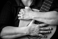 Hands hugging an acoustic guitar Royalty Free Stock Photography