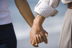 Hands of husband and wife holding stock image