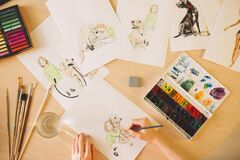 The hands of an illustrator painter draw a storyboard for a movie or cartoon, top view