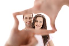 Hands imitating frame for couple photo. In focus, couple smiling at camera in studio royalty free stock images