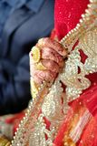 Hands of an Indian bride adorned with jewelery and wedding ring Royalty Free Stock Photo