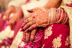 Hands of an Indian Bride, Mehndi or Henna during a wedding ceremony. Hands of an Indian Bride, tattooed with natural and local dye, Mehndi or Henna during a stock image