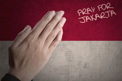 Hands with Indonesian flag pray for Jakarta Royalty Free Stock Photos