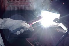 Hands of industrial worker with torch welding metal steel with spark in workshop. Hands of industrial worker with torch welding metal steel with spark in Royalty Free Stock Photography
