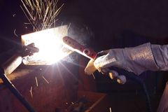 Hands of industrial worker with torch welding metal steel with spark in workshop. Hands of industrial worker with torch welding metal steel with spark in Stock Photos