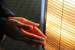 Warming cold hands. Hands with injured finger warming in front of a heater Stock Images