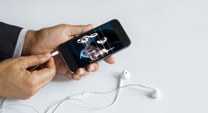 Hands insert earphone jack to smartphone Royalty Free Stock Image