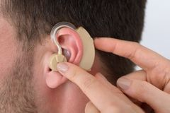 Hands inserting a hearing aid into a man's ear stock image