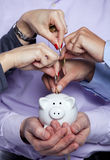 Hands inserting money in the piggybank Royalty Free Stock Image