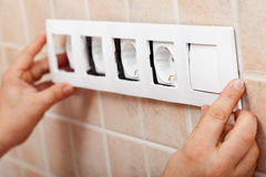 Hands installing decorative frame on electrical sockets Royalty Free Stock Photos
