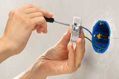 Hands installing electrical wall socket with screwdriver Royalty Free Stock Photo