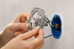 Hands installing light switch in plasterboard wall Stock Photo