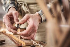 Hands of an instrument maker working on a violin bow stock photos