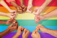 Hands of international people showing thumbs up. International, diversity, gay pride, tolerance and people concept - hands showing thumbs up over rainbow Royalty Free Stock Image