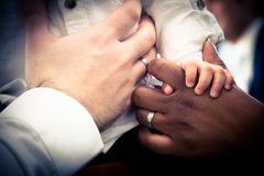 Hands of Interracial couple with child Stock Image
