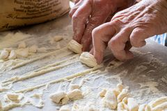 Hands of Italian woman making traditional fresh pasta on a marble table stock photography