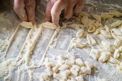 Hands of Italian woman making traditional fresh pasta on a marble table stock image