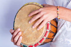 Hands on the jambe. Medium sized jambe on the laps of performer. Artist's hands are rested on the instrument Royalty Free Stock Images