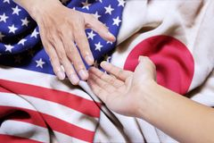 Hands with Japan and  USA flag. Hand of a person offering a help for somebody with Japan and  USA flag in the background Royalty Free Stock Photo