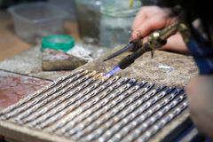 Hands of jeweller at work silver soldering. Goldsmith working and welding Royalty Free Stock Image