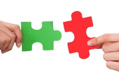 Hands joining jigsaw puzzle pieces Royalty Free Stock Image