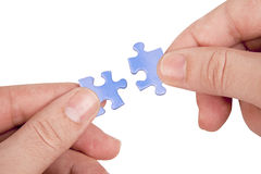 Hands joining puzzle pieces Royalty Free Stock Photo