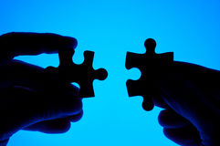 Hands joining puzzle pieces. Royalty Free Stock Photography