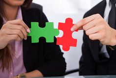 Hands joining puzzle pieces. Cropped image of hands joining puzzle pieces Stock Images
