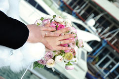 Hands of just married on wedding bouquet. With the sea and yacht Stock Images