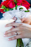 Hands of just married woman holding bouqet Stock Photos