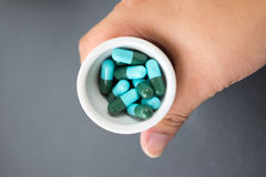 Hands keep heap of blue green round capsule. Female hands keep heap of blue green round capsule Stock Image