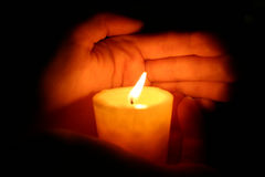 Hands keeps candle. Hands keeps burninging candle in the dark Royalty Free Stock Image