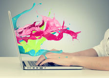 Hands on keyboard with colorful splashes out of monitor Royalty Free Stock Photography