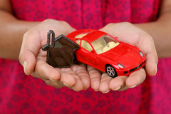 Hands with keys and red toycar Stock Image