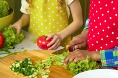 Hands of kid cooking. Chopped lettuce and cucumber Royalty Free Stock Photo