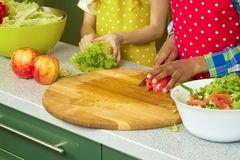 Hands of kid cutting tomato. Fresh vegetable on cooking board Stock Image