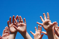 Hands of kids. Lots of little hands of caucasian white children raising up their arms into the blue sky outdoors Royalty Free Stock Images