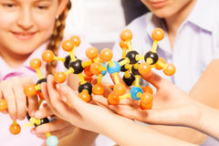 Hands of kids assembling molecule model at lab. Hands of young students assembling molecule models for science project Stock Photography