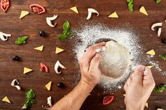 Hands knead the dough for pizza making. On wooden table Stock Photos