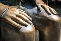 Hands on knees sculpture - bronze statue Stock Photo