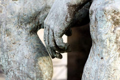 Hands on knees. Sculpture : detail of a big statue of a naked man sitting on a grave in the cemetery of Montmartre in Paris in France royalty free stock images