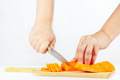 Hands with a knife chops carrots on a wooden cutting board Stock Photos