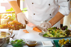 Hands with knife cut fish. Stock Photo