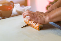 Hands with knife cut sushi. Royalty Free Stock Image