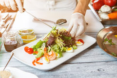 Hands with knife make salad. Stock Photo