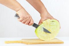 Hands with a knife shred cabbage on a cutting board. Close up Stock Images