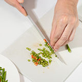 Hands and knife for slice pepper on plastic plate block Stock Images