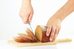 Hands with a knife sliced rye bread on a cutting board Stock Photography