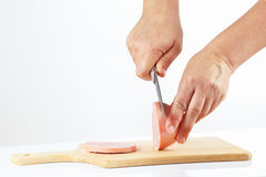 Hands with a knife sliced sausage Royalty Free Stock Image