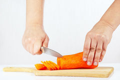 Hands with a knife slices carrots on a cutting board Royalty Free Stock Photos